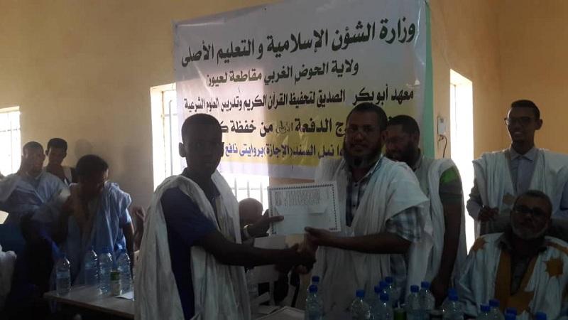 أحد خريجي المعهد يتسلم شهادة تكريمه خلال الحفل