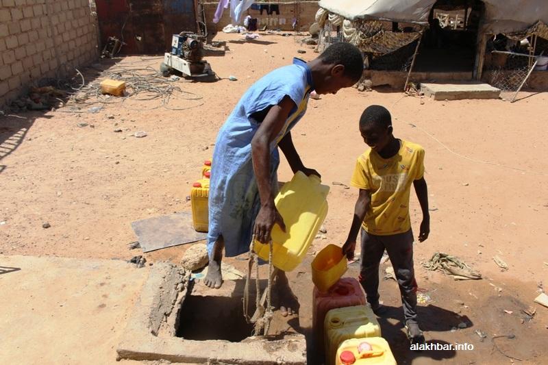 أطفال يستخرجون مياه الشرب من أحد الآبار في المدينة في صيف العام المنصرم (الأخبار - أرشيف)
