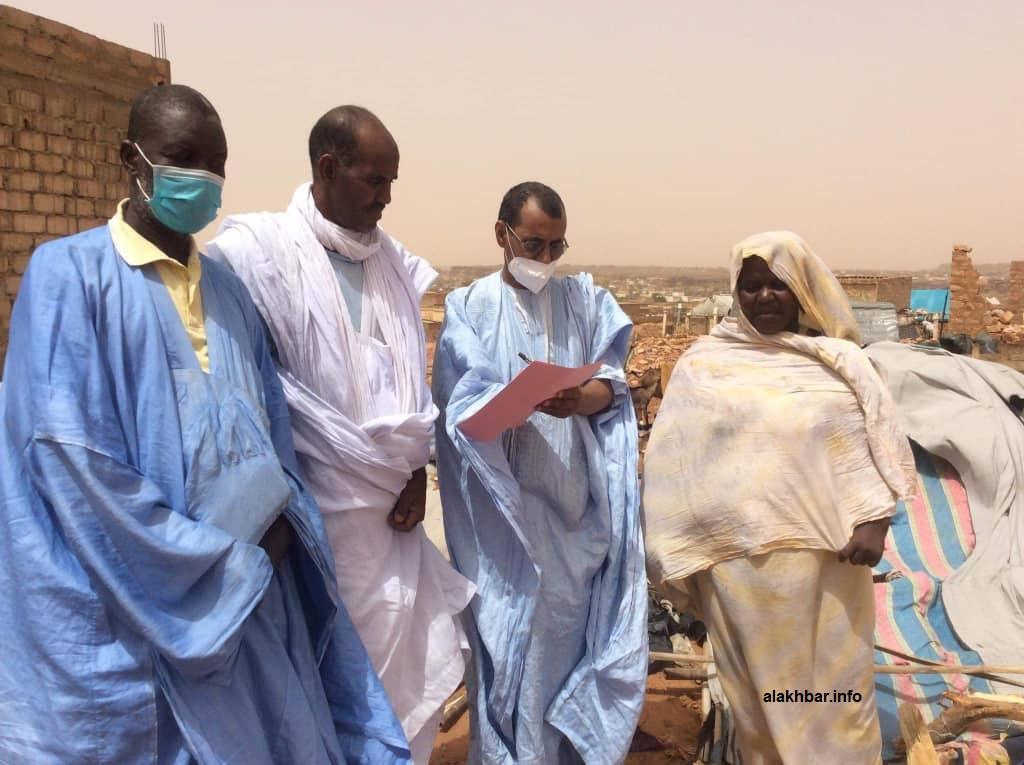 عمدة العيون اج ولد الدي خلال زيارته ومساعديه لإحدى الأسر المتضررة جراء العاصفة