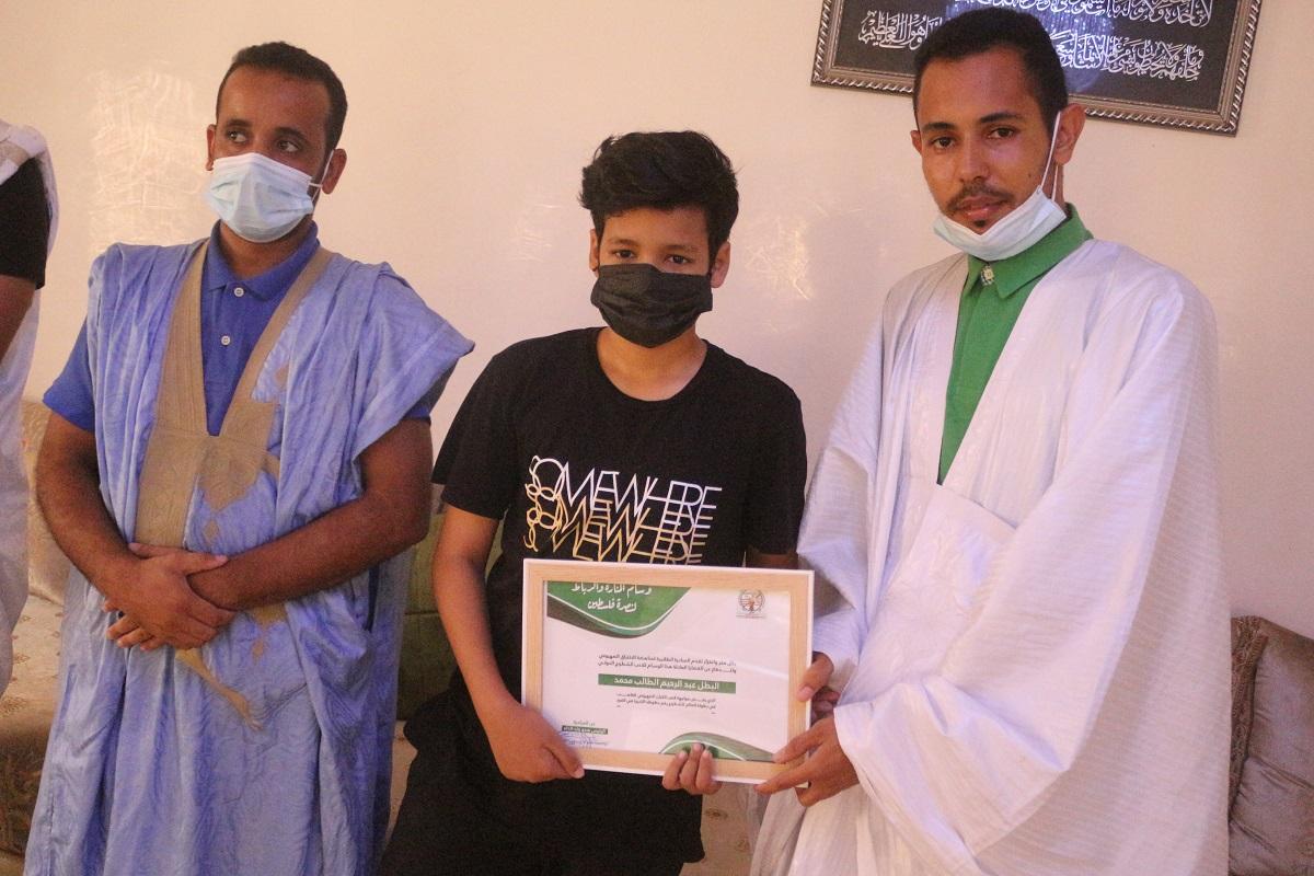 رئيس المبادرة هدو ولد الداه خلال تسليم وسام التكريم للطفل عبد الرحيم الطالب محمد