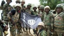 """جنود نيجيريون مع علم جماعة """"بوكوحرام"""" بعد تفكيكهم معسكرا للمجموعة خلال فبراير 2017."""