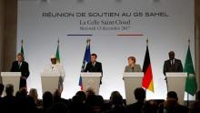 الرئيس الفرنسي إيمانويل ماكرون وبعض المشاركين بقمة باريس خلال مؤتمر صحفي في ختام القمة.