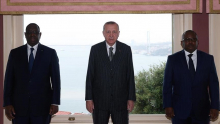 الرئيس التركي يقف بين ضيفيه اليوم السبت