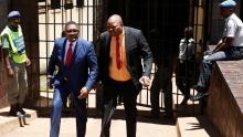 وولتر مزامبي الوزير السابق للشؤون الخارجية الزيمبابوي ومحاميه جوب سيخالا لدى الخروج من المحكمة.